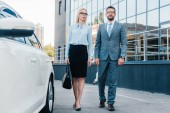business people in eyeglasses walking to car on parking
