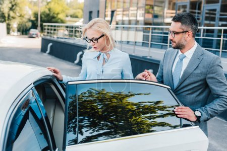 portrait of businessman helping colleague sit into car on street