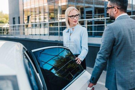 businessman opening car door for colleague on parking