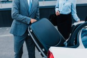 cropped shot of businessman putting baggage into car with colleague near by