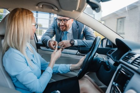 smiling businessman giving car keys to colleague at driver seat in car