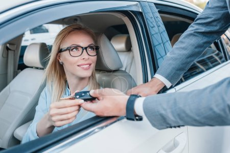 partial view of businessman giving car keys to smiling colleague at driver seat in car
