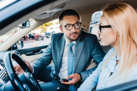 selective focus of business colleagues looking at each other in car