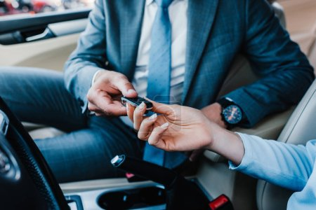 cropped shot of businessman giving car keys to colleague at driver seat in car