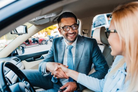 selective focus of smiling business colleagues shaking hands in car