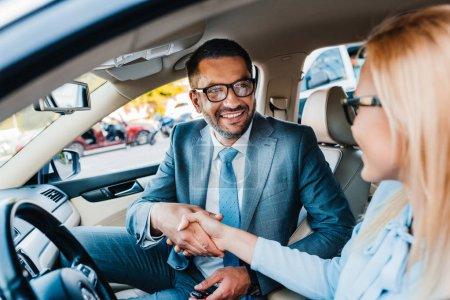 Photo pour Foyer sélectif de souriants collègues d'affaires serrant la main dans la voiture - image libre de droit