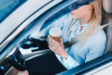 high angle view of blonde businesswoman with coffee to go driving car