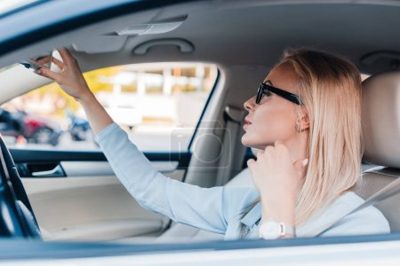 side view of blonde businesswoman in eyeglasses looking at rear view mirror in car