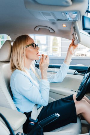 side view of attractive businesswoman applying lipstick in car