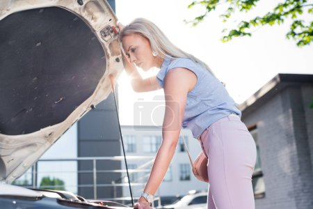 side view of pensive woman looking under car hood of broken car on street
