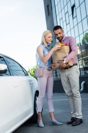 married couple with paper bag full of healthy food on parking near car