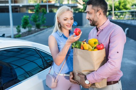 portrait of smiling married couple with paper bag full of healthy food on parking near car