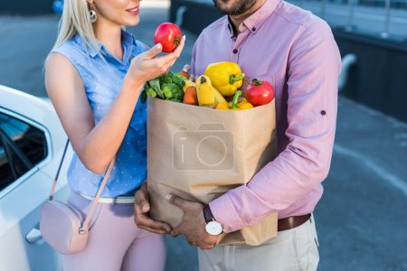 cropped shot of couple with paper bag full of healthy food on parking near car