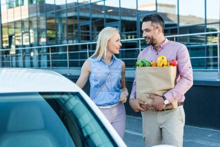 portrait of married couple with paper bag full of healthy food on parking near car
