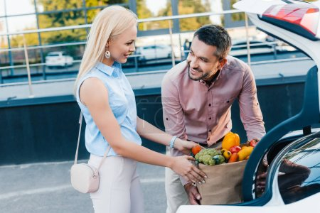 portrait of married couple putting paper bag full of healthy food into car on parking