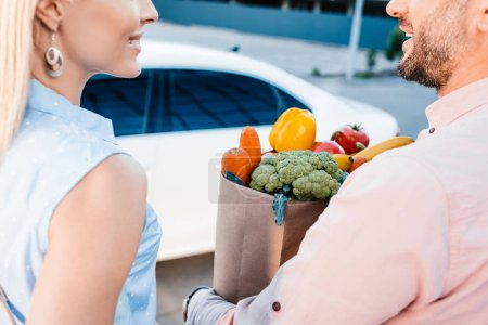 cropped shot of married couple with paper bag full of healthy food on parking near car