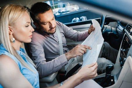 Photo pour Vue latérale du couple à la recherche d'une destination sur la carte assis en voiture - image libre de droit