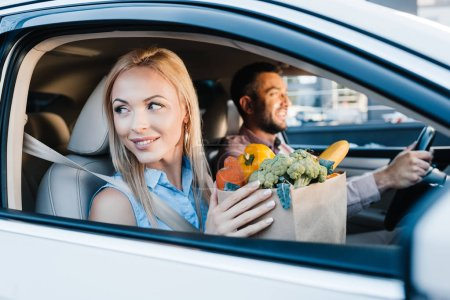selective focus of married couple with paper bag full of healthy food in car