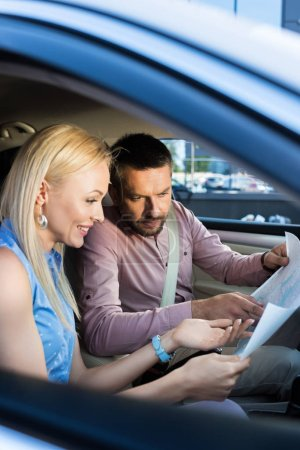side view of couple looking for destination on map while sitting in car