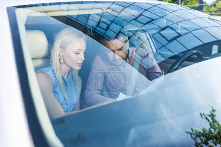 couple looking for destination on map while sitting in car