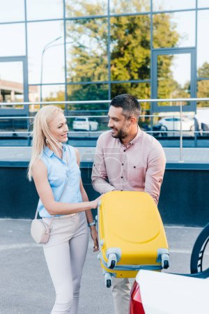 smiling married couple putting luggage into car on parking