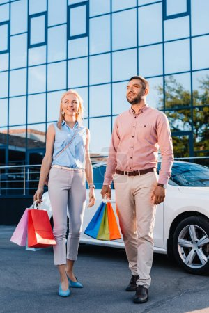 smiling married couple with shopping bags standing near car on street
