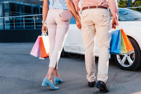 partial view of married couple with shopping bags holding hands while walking to car on street