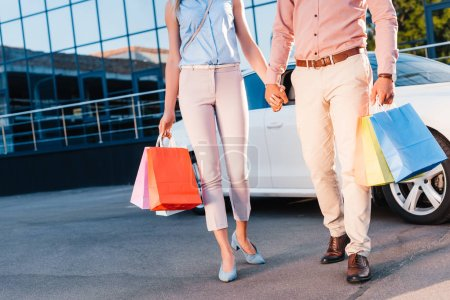 partial view of married couple with shopping bags holding hands while walking on street