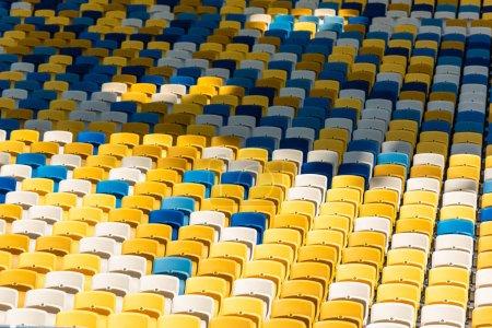 full frame shot of empty colorful seats on tribunes of modern stadium