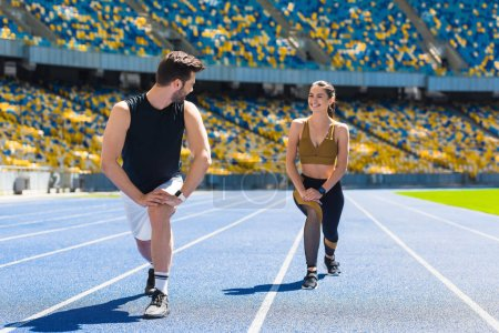 young fit couple warming up legs before jogging on running track at sports stadium