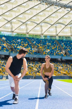 young athletic couple warming up legs before jogging on running track at sports stadium