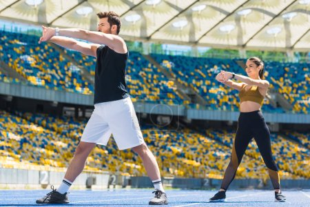 young beautiful couple warming up before training on running track at sports stadium