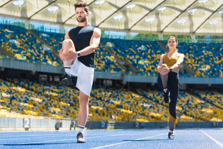 young sportive couple warming up legs before jogging on running track at sports stadium