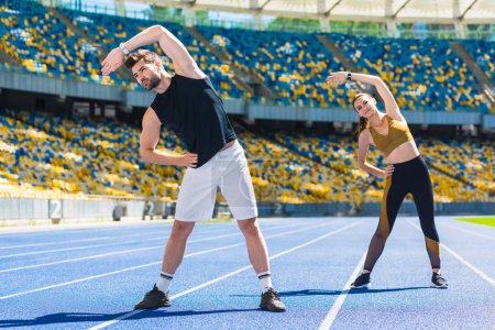 young sportive couple doing side bend before training on running track at sports stadium