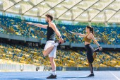 young active couple warming up before training on running track at sports stadium
