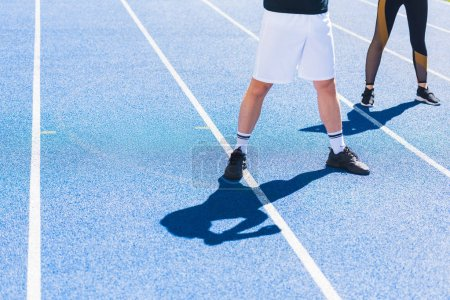 cropped shot of man and woman in modern sportswear standing on running track