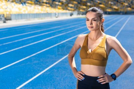 athletic female jogger with arms akimbo on running track at sports stadium
