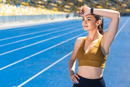 athletic female jogger wiping sweat after run on track at sports stadium
