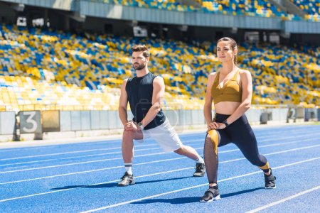 young fit couple warming up before training on running track at sports stadium
