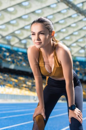 fit young woman resting after jogging on running track at sports stadium