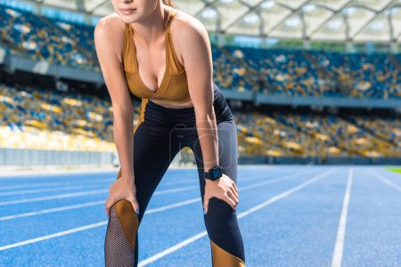 athletic young woman resting after jogging on running track at sports stadium
