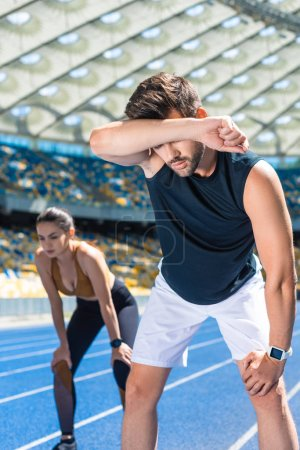 young exhausted couple standing on running track at sports stadium after jogging