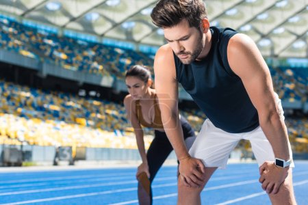 young tired couple standing on running track at sports stadium after jogging