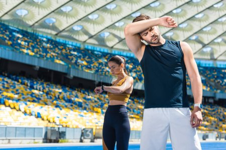 exhausted couple standing on running track at sports stadium after jogging