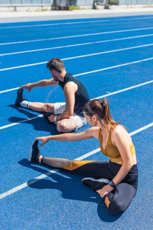 high angle view of young athletic male and female joggers sitting on running track and stretching