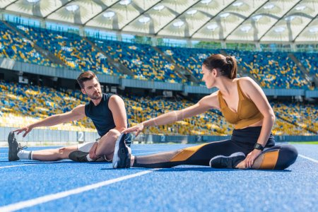 young fit male and female joggers sitting on running track and stretching at sports stadium