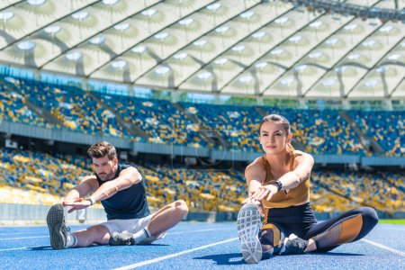 young sportive male and female joggers sitting on running track and stretching at sports stadium