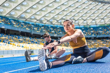 young male and female joggers sitting on running track and stretching at sports stadium
