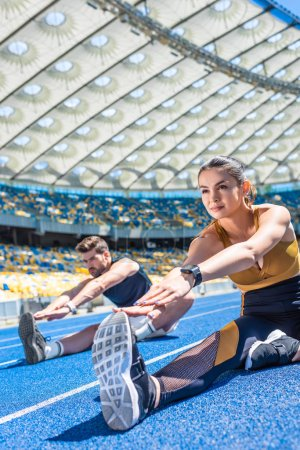 young attractive couple sitting on running track and stretching at sports stadium