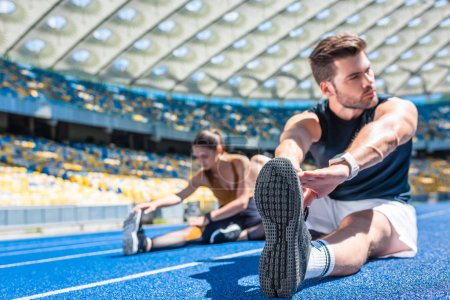 young athletic couple sitting on running track and stretching at sports stadium